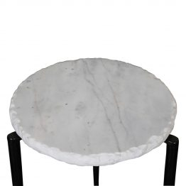 White marble side table with chiseled edges on black metal base