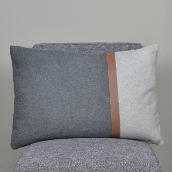 gray and white lumbar pillow with brown leather stripe